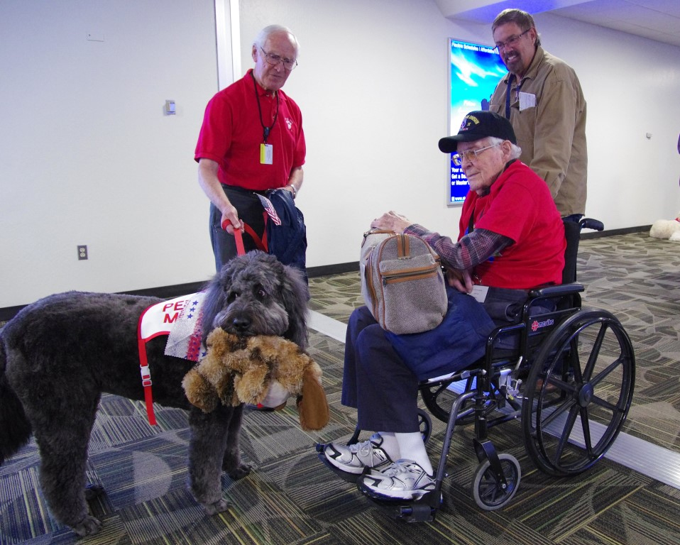 Nellie Belle shows her new friends her favorite stuffed toy at the airport.